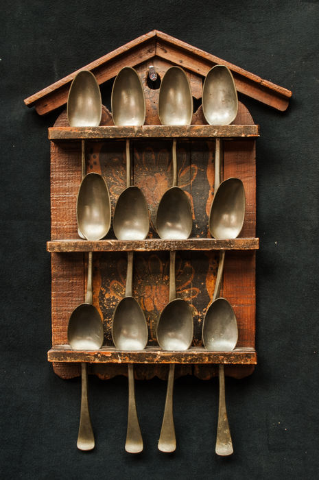 A 19th-century Frisian painted wooden spoon rack with 12 antique pewter spoons.