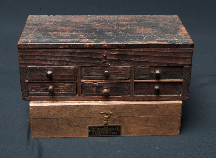 """A 19th century watchmaker's chest with 6 drawers and a box containing 36 corked bottles and labeled """"Faddegon and Krook Amsterdam"""""""
