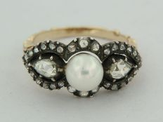Gold with silver ring, set with a central cultivated pearl and an entourage of rose cut diamonds.