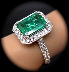 18 kt white gold ring, with emerald surrounded by diamonds.