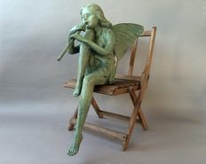 A large bronze statue of an elf with a flute