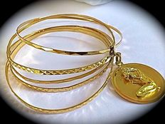 Gold rigid bracelet with 5 rings and Zodiac medallion in 18 kt gold.