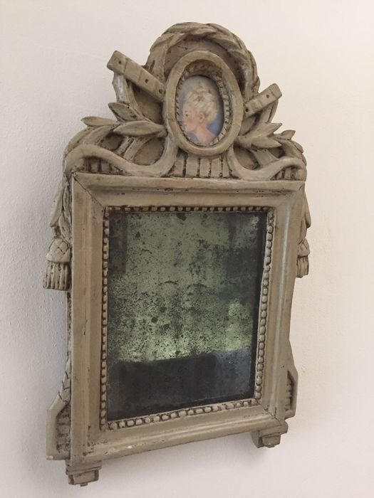 An attractive Lodewijk XVI style wooden mirror with weathered glass, a portrait in the crest, and with the original mirror glass - France - circa 1850