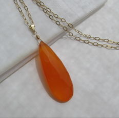 Gold necklace with large faceted chalcedony in mandarin orange.