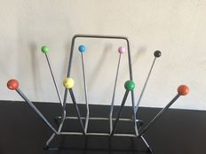 A retro metal magazine rack with painted wood knobs