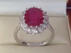 White gold 18 kt entourage ring with a 4.01 ct ruby and 14 diamonds