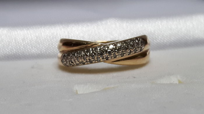 Gold crossover ring with diamond.