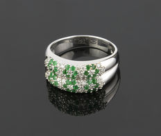 White gold cocktail ring in a flowers design, set with diamonds and emerald gemstones in head.