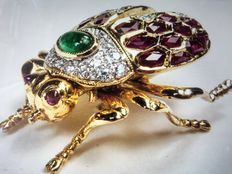 Brooch in 18 kt gold with diamonds, rubies and an emerald in the shape of a scarab beetle.