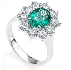 White-gold ring with central emerald surrounded by diamonds.
