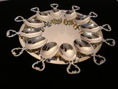 Silver plated round charger plate with 12 silver-plated decorated appetizer spoons, approximately 3rd quarter of the  20th century. France