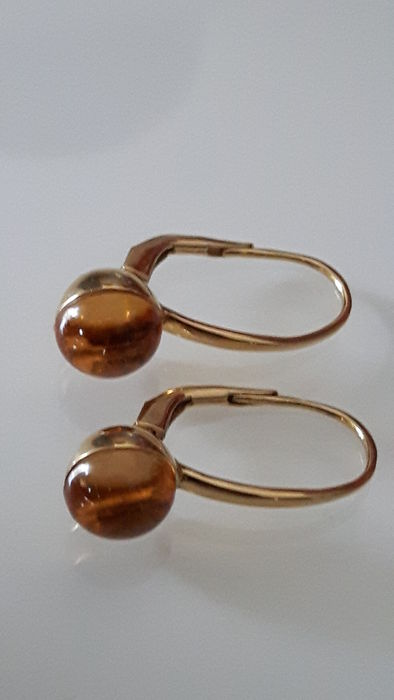 Gold earrings with cabochon cut citrine gemstones.