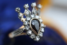 Ring in the shape of a crown with garnet and rose cut diamonds.
