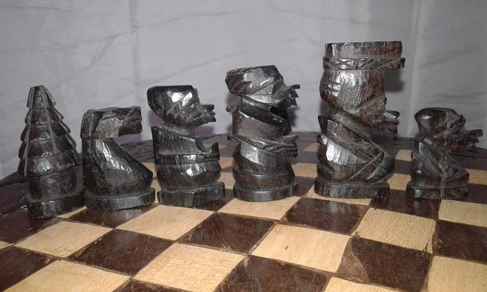 African Hand Carved Ebony Wood Chess Set On Table With Two