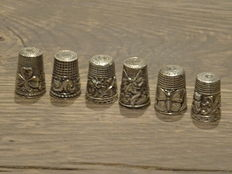 Six silver thimbles with various images, among others a butterfly - cat - winged elf - etcetera