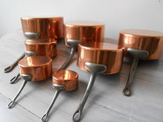 Seven copper saucepans