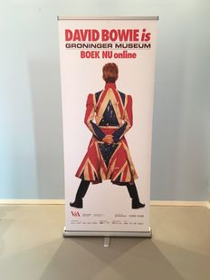 Exhibition banner for 'David Bowie is' with image of David Bowie in Union Jack coat for 'The Earthling'