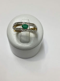 2-tone gold ring set with an emerald and diamonds.
