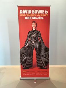 Exhibition banner for 'David Bowie is' with image of David Bowie in Yamamoto bodysuit