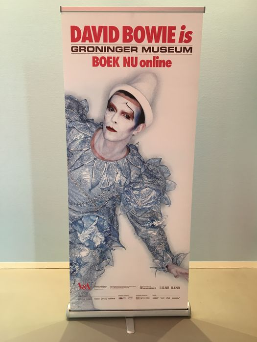 Exhibition banner for 'David Bowie is' with image of David Bowie's 'Ashes to Ashes'