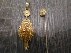 Gold pendant with matching tie pin.