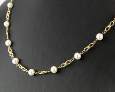 Yellow gold necklace, composed of 18 Akoya cultured pearls spaced out along the chain