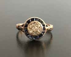 Luminous art deco ring made of 18 kt gold ornamented with calibrated sapphires and diamond roses