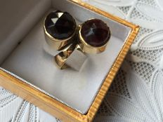Heavy, gold ring with two faceted cut garnets