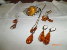 Lot consisting of: 2 silver pendants with necklace, 2 pairs of amber silver earrings and bracelet with amber and silver