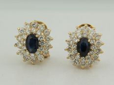 Gold clip-on earrings with central sapphire and double entourage of brilliant cut diamonds