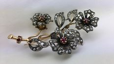 Gold brooch with diamonds and rubies, in a branch design with flowers and leaves.