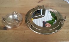 Old brass porthole with mirror that can open and a glass porthole ashtray which also opens.