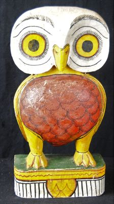 Large wooden statue in the shape of a decorative, colourful painted owl