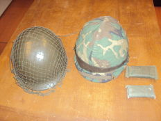 Steel battle helmets with camouflage netting, including complete helmet interior - complete items. Two pieces with 2x first aid bandage.