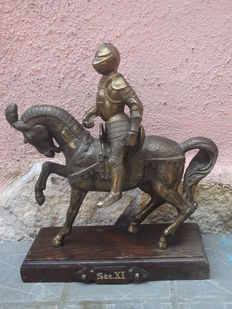 A bronzed solid metal figure Knight on horseback