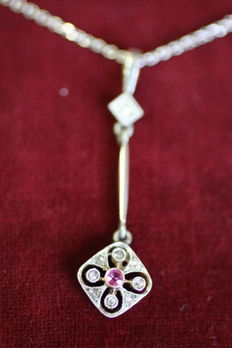 Gemstone pendant with gold necklace.