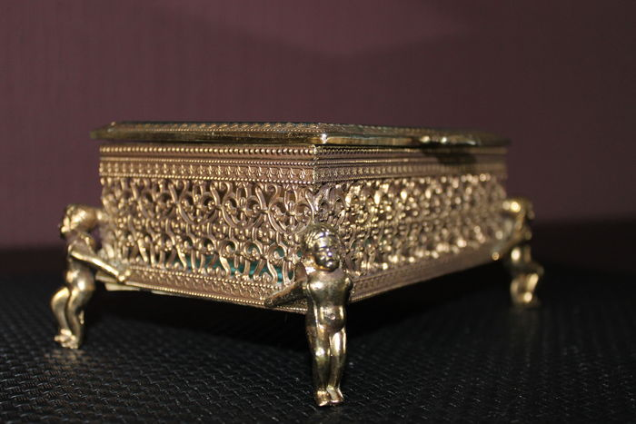 Vintage gilt ormolu filigree jewellery box with angel feet with bevelled glass lid