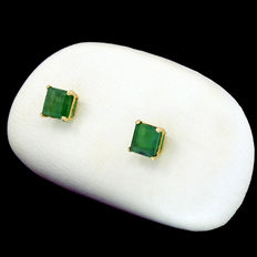 Yellow gold earrings and two princess cut emeralds.
