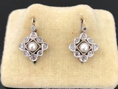 Pair of dangling earrings, from the '20s, in 18 kt gold, with pearls in the center surrounded with diamonds.
