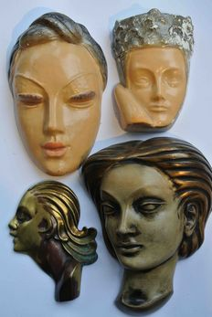 Four Art Deco style female heads, (wall decoration), of plaster and brass