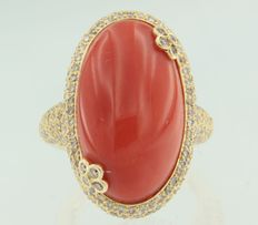 Yellow gold ring 18 kt, set with a central, cabochon, oval cut coral and 310 brilliant cut diamonds.