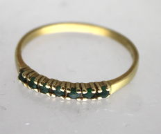 Yellow gold ring with green zirconia  stones.