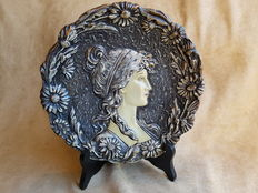 Art Nouveau wall plate with relief decoration of female head, in the style of Alphonse Mucha