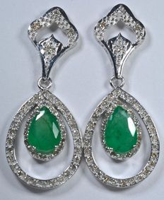 Earrings set with 104 diamonds weighing 0.73 ct and with two natural emeralds in a droplet cut weighing 2 ct.