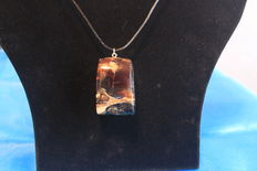 Large amber pendant with inclusions, blue and cognac coloured, tooled by hand