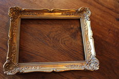 A hand-gilded picture frame and gilt metal photo frame