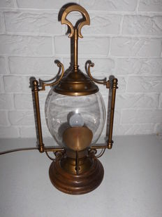 Stylish large brass ship lamp with a beautiful appearance, on wooden base