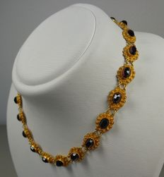 Gold link necklace with garnets.