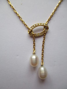 A gold necklace with diamond and two pearls.