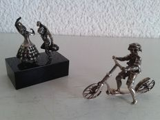 Silver miniature of dancing couple on a marble base and silver miniature child on scooter.